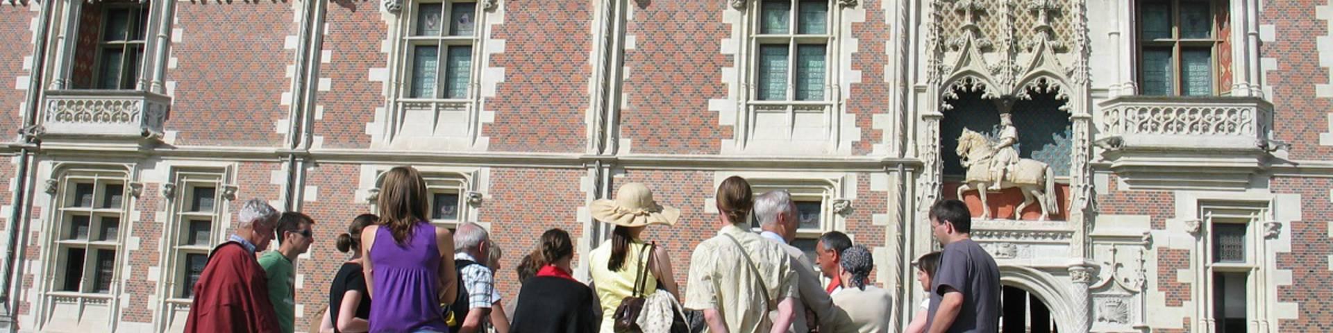 Grupo de turistas con un guía en la plaza del castillo de Blois. © OTBC